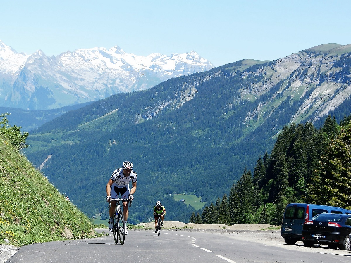 Cyclists climbing to the top of a mountain in the French Alps with snow in background