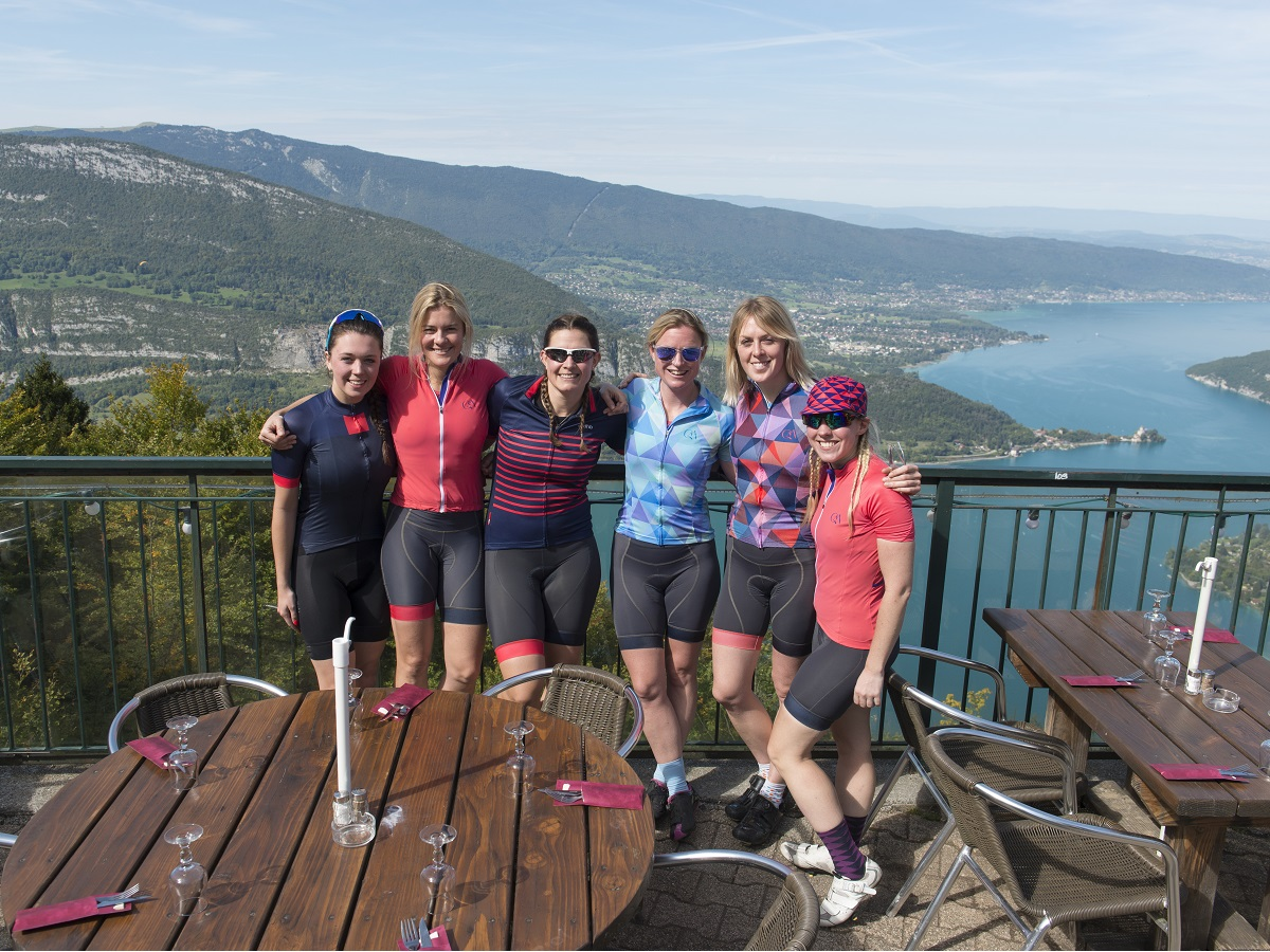 Cyclists at a cafe overlooking Lake Annecy with mountains in background