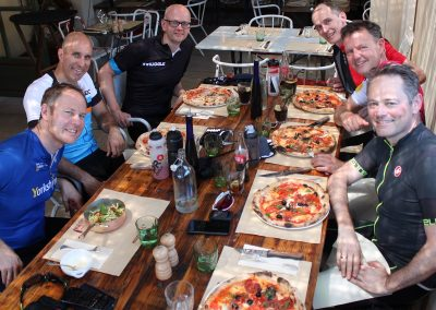 Male cyclists smiling whilst eating pizza