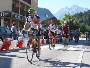 Cyclists riding through a village with mountains